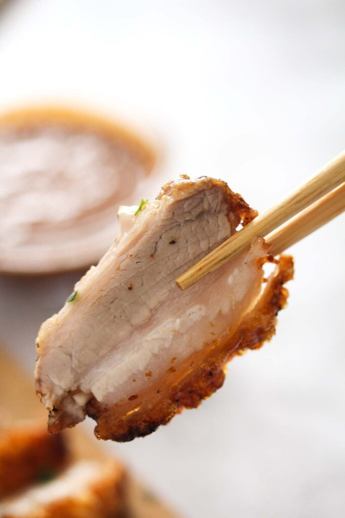 chopsticks holding a piece of crispy pork belly.
