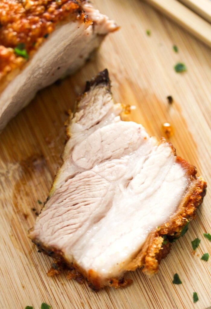 close up of a slice of pork belly with crispy crackling on a board.