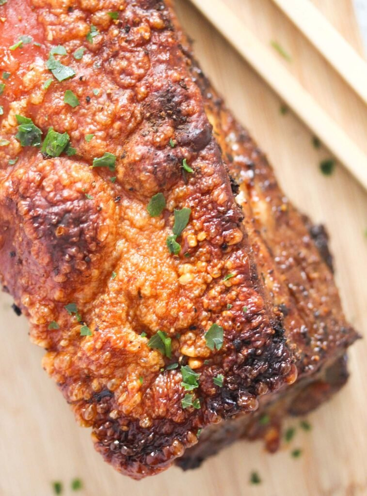 whole piece of pork with crispy crackling on a wooden board sprinkled with parsley.