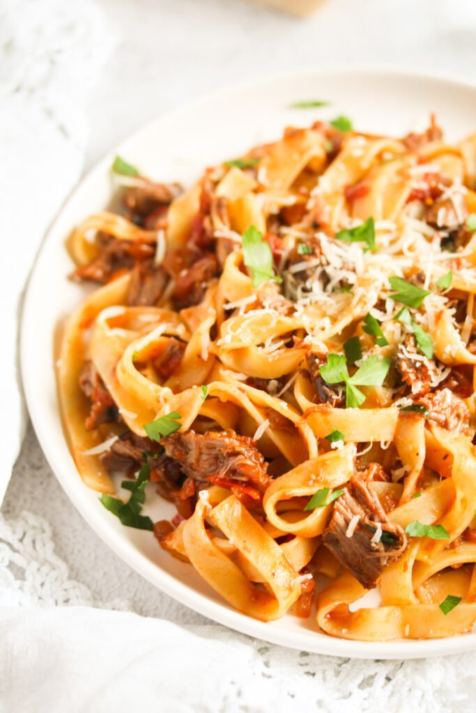 pappardelle with lamb ragout on a plate sprinkled with parmesan.