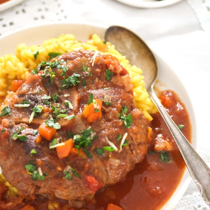 osso buco with risotto milanese and gremolata on a plate.
