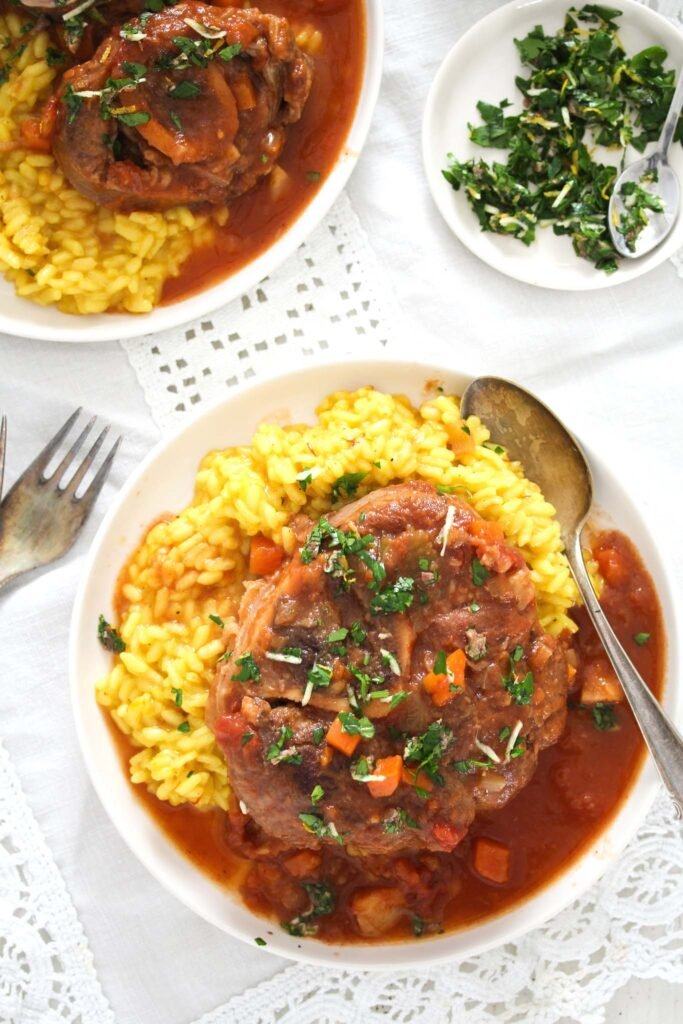 small plates with osso buco served with sauce and risotto milanese. small plate of gremolata beside.