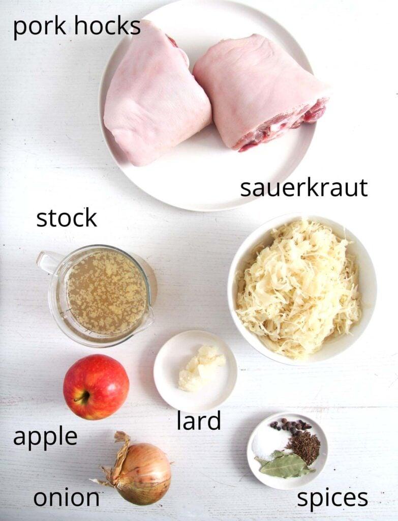 ingredients for cooking knuckles. two pork hocks, sauerkraut, stock, apple, lard, spices, onion.