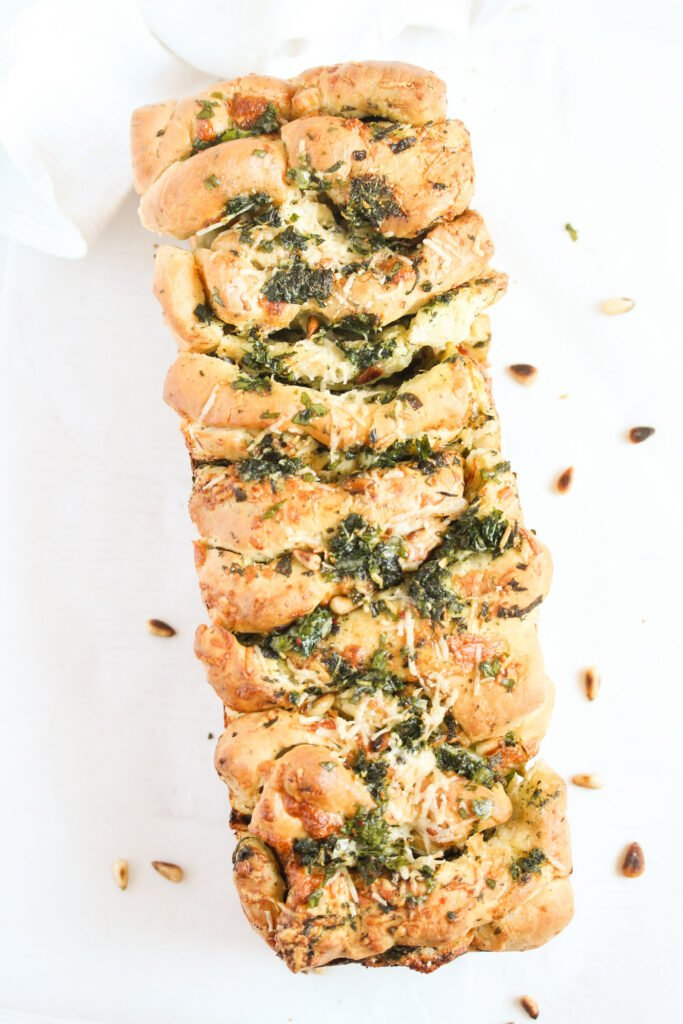ramsons bread with parmesan and herbs on a white table.