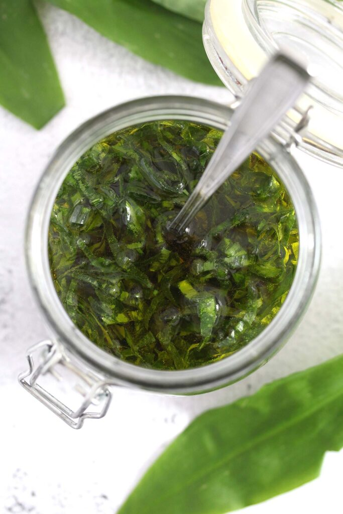 steeping infused oil with herbs in a jar.
