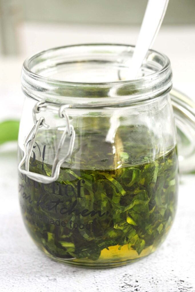 chopped ramsons leaves in a jar with olive oil.