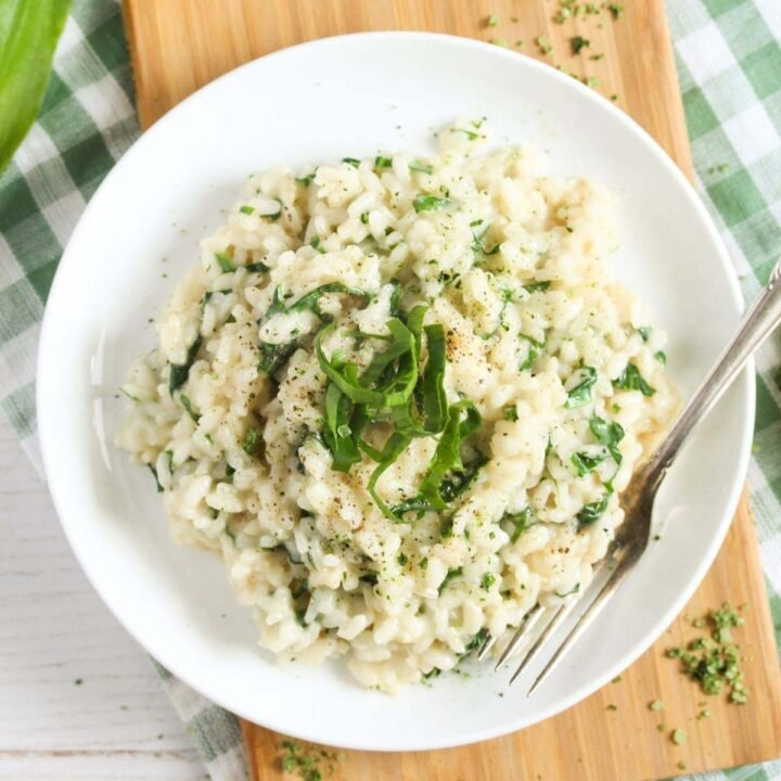 wild garlic risotto with parmesan on a small white plate.