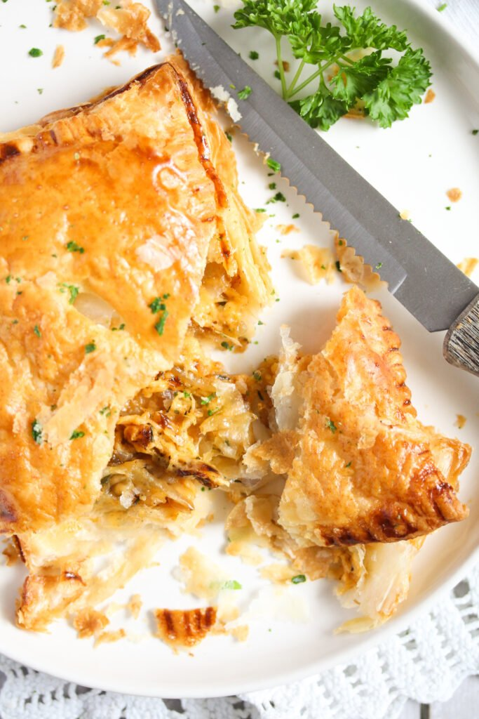 cutting a cheese and onion pasty with a small knife.