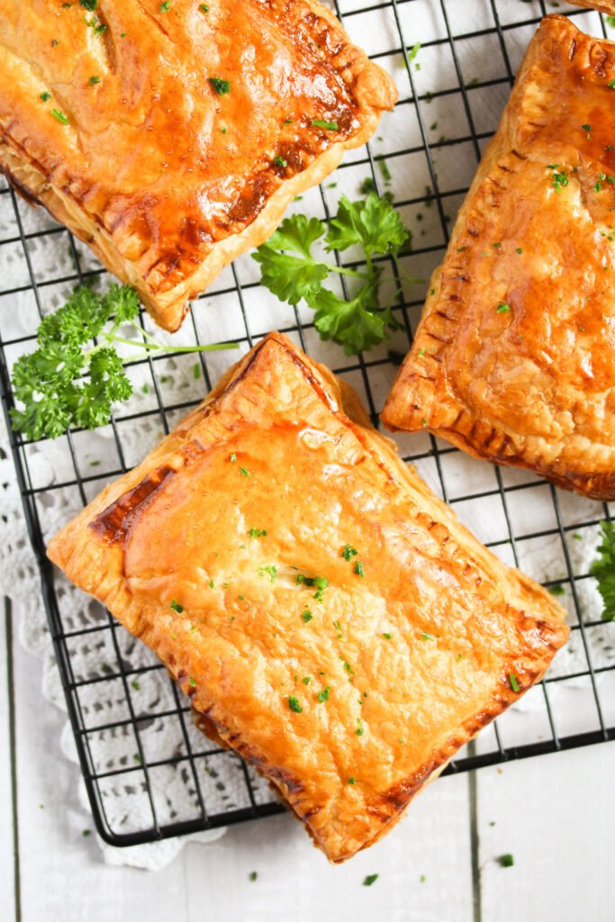 puff pastry slices with cheese on a wire rack.