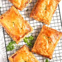 large cheese and onion pasties cooling on a wire rack with a few sprigs of parsley between them.