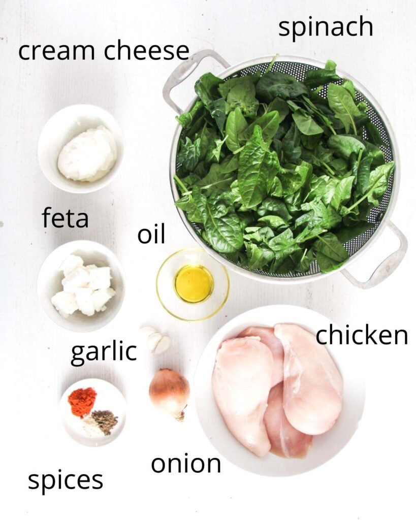 fresh spinach, cream cheese, feta, oil, garlic, spices, chicken breast, onion arrranged on a table.