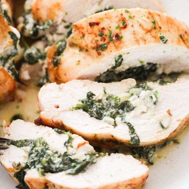 spinach stuffed chicken breast sliced on a plate.