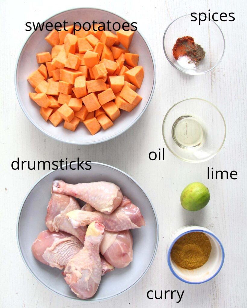 bowl of cubed sweet potatoes, raw chicken pieces, curry, spices, lime, oil.