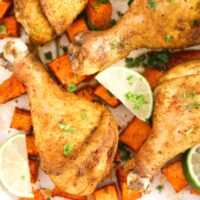 several curry drumsticks with sweet potato pieces and lime wedges in between.