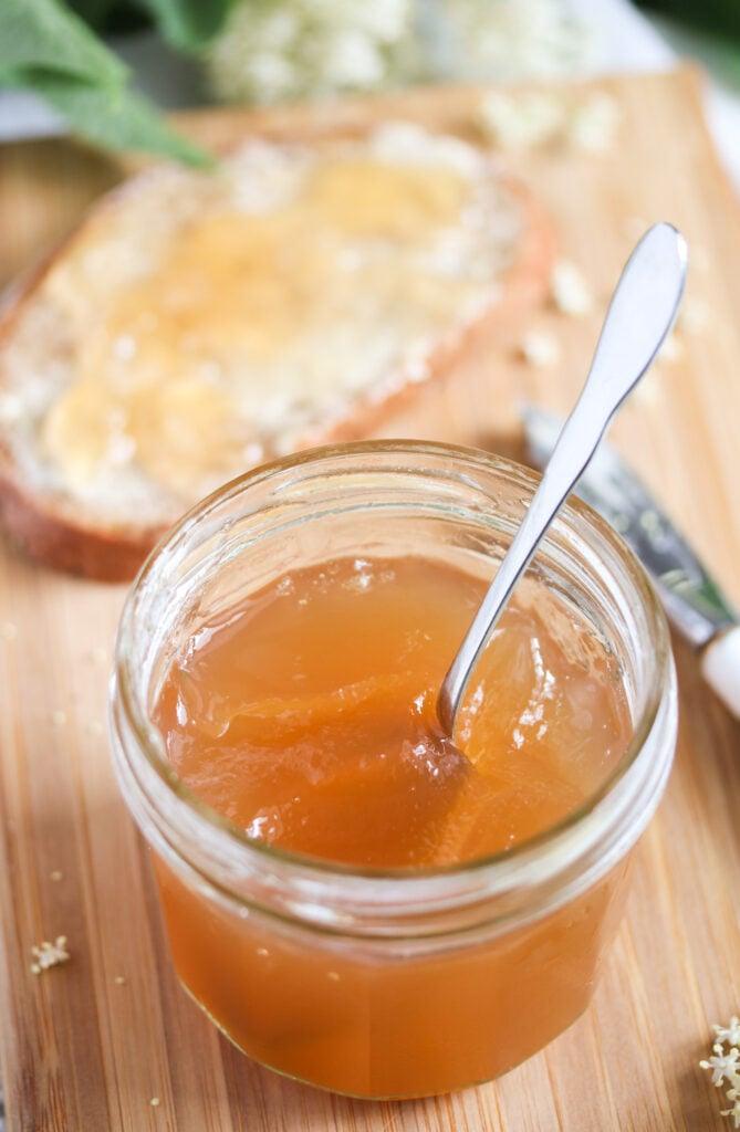 elderflower jam made with apple juice in a jar. slice of bread behind it.