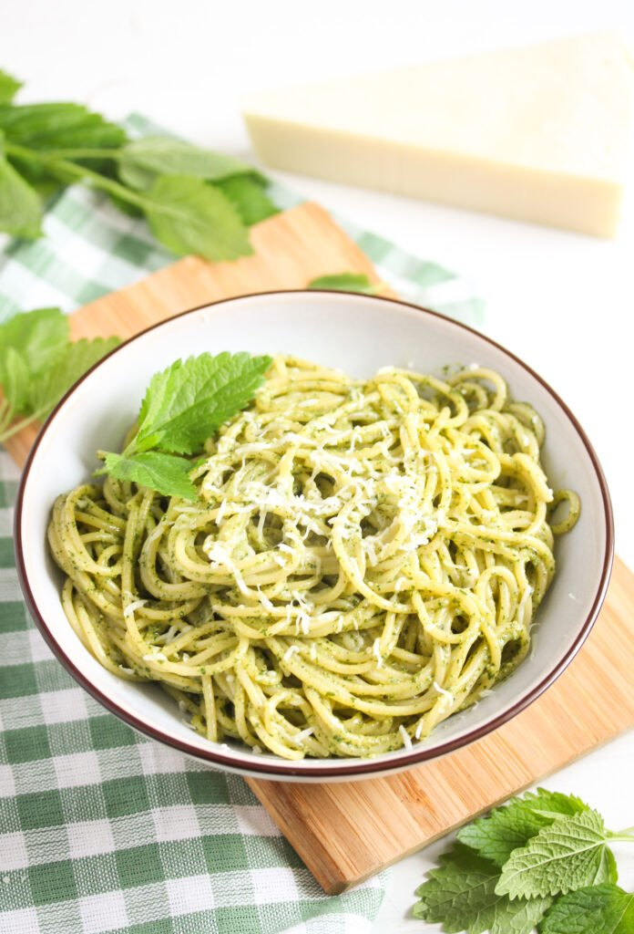 lemon balm pasta in a small bowl with fresh leaves around it.