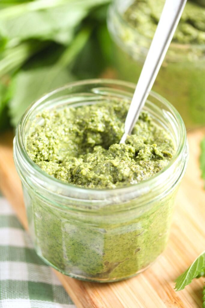 small jar of lemon balm pesto with a spoon in it.
