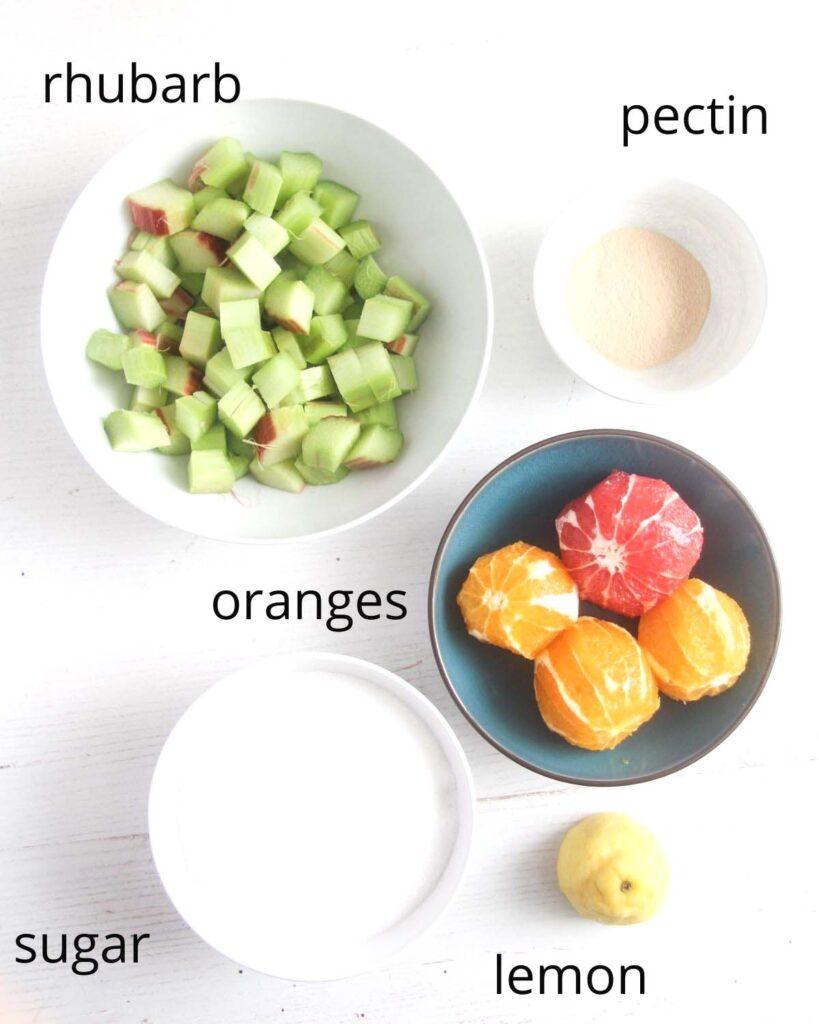 chopped rhubarb, peeled oranges, sugar, lemon and pectin in bowls on the table.