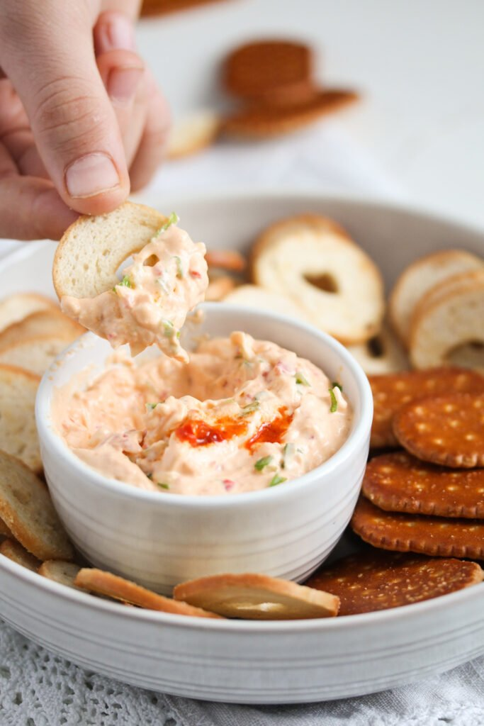 peri peri dip in a small bowl and a hand dipping a cracker in it.