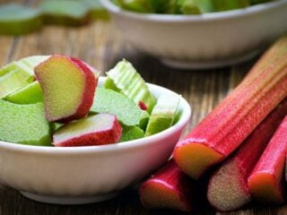 rhubarb stalks and two bowls of chopped rhubarb on a wooden table.