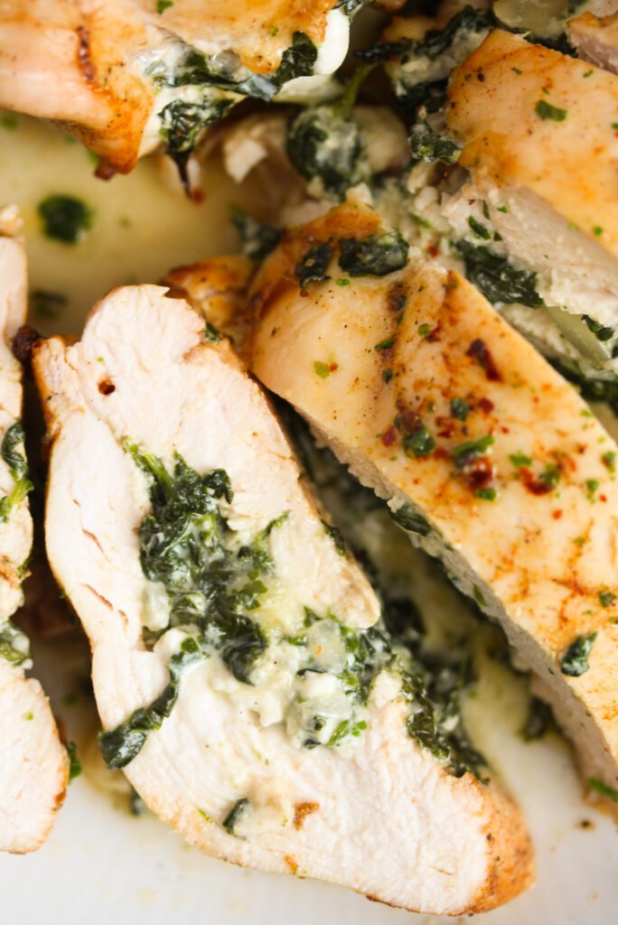chicken breast stuffed with spinach and cream cheese sliced on a platter.