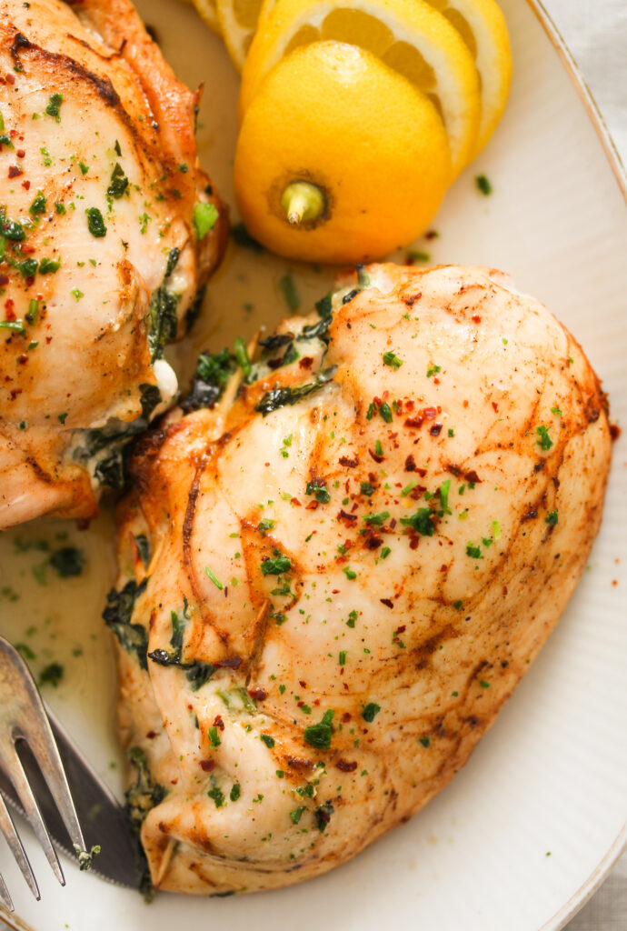 close up of one and a half cooked poultry breasts with lemon slices.