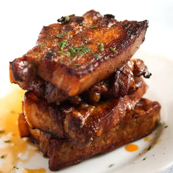 stapled sliced pork belly slices sprinkled with parsley, pool of fat in the back.