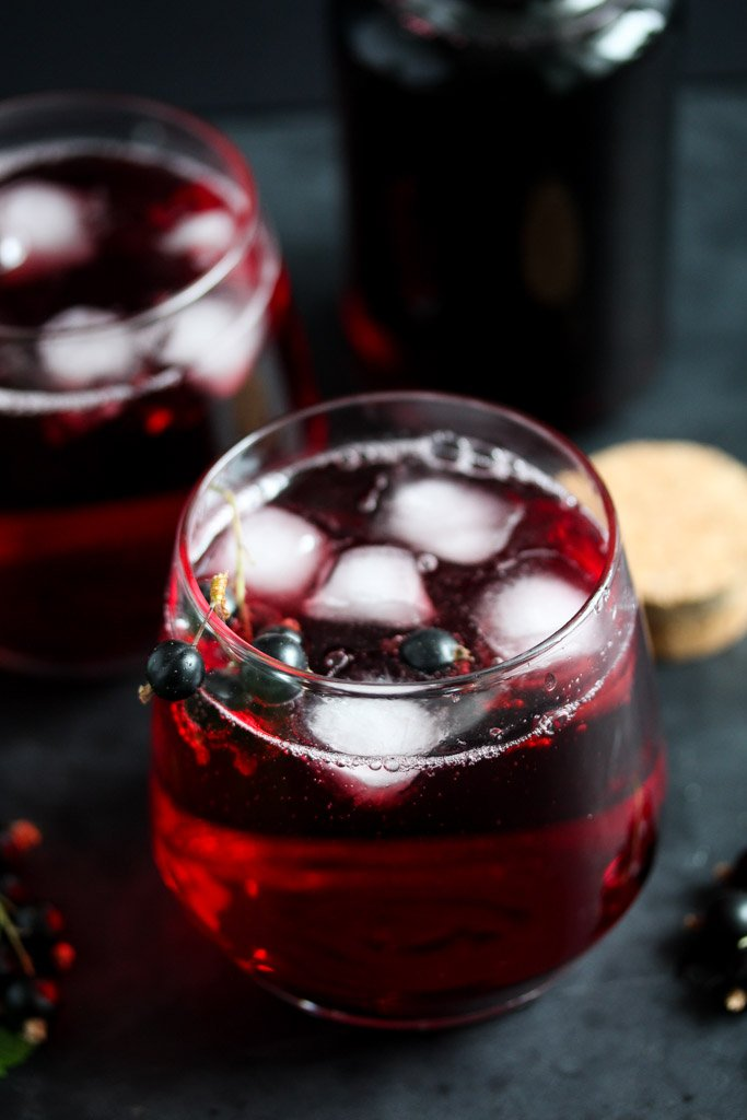 two glasses of diluted black currant syrup served with ice and a bottle behind.