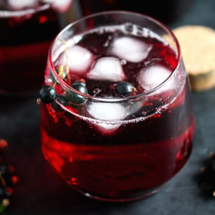 small glass with blackcurrant cordial with ice cubes.