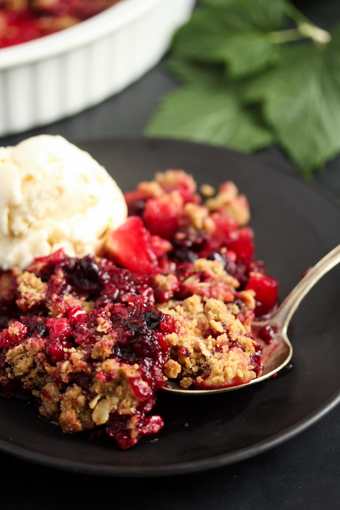crumbles and currants served with ice cream on a black plate with a spoon.