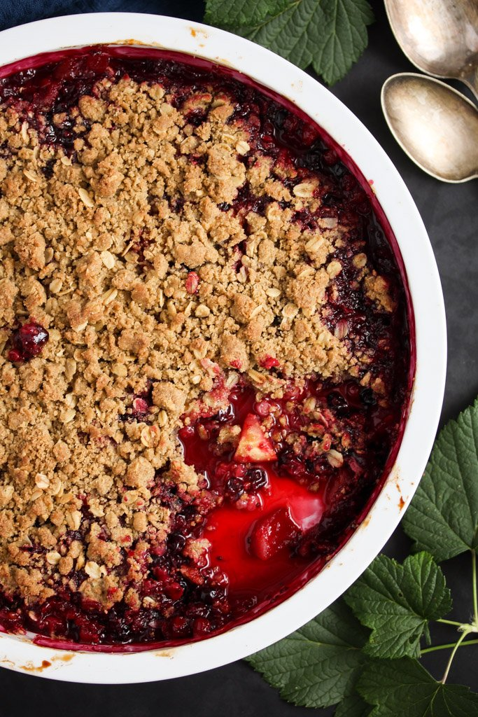 close up baking dish with currant crumble on a dark background, two tablespoons beside it.