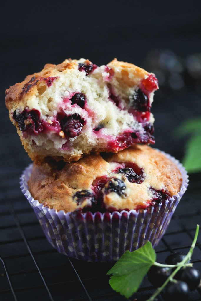 two stapled black currant muffins, one of them split showing the juicy berries inside.