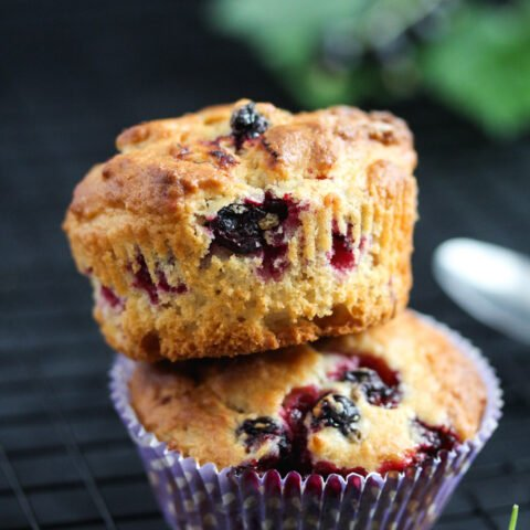 two stapled black currant muffins with leaves behind.