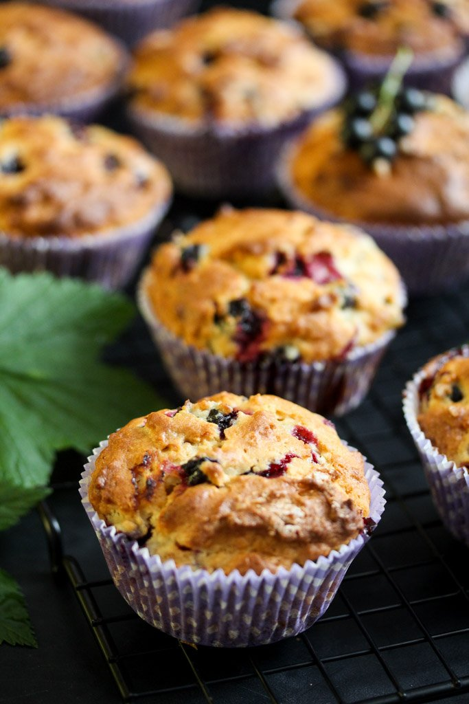 many berry cupcakes on a black table with leaves beside.
