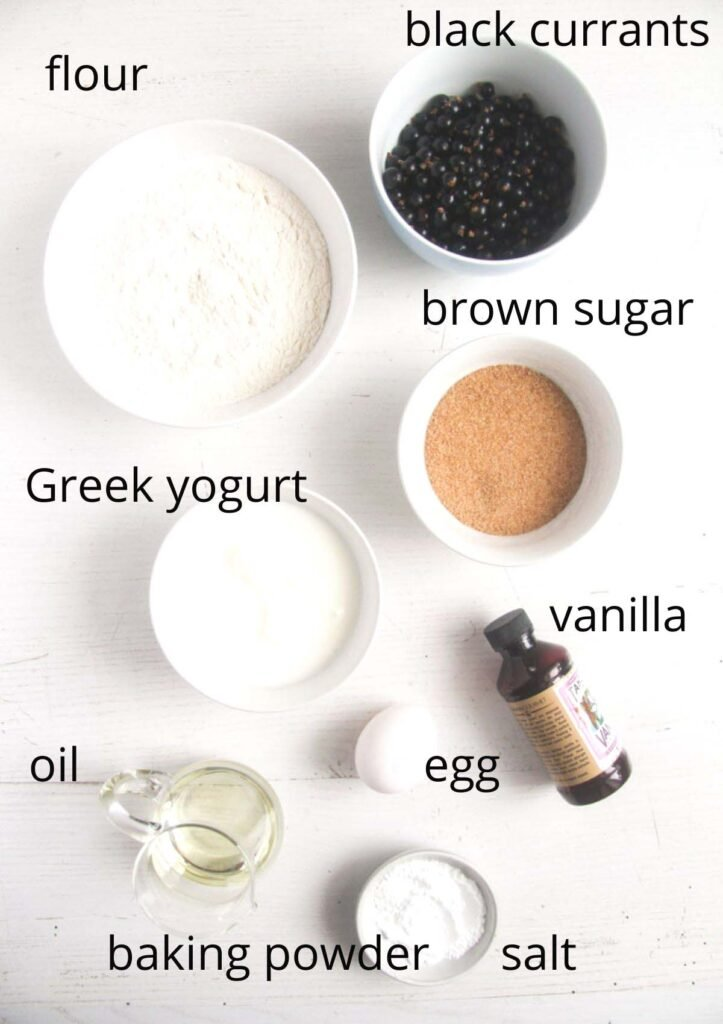 bowls with flour, currans, yogurt, sugar, vanilla, egg, oil, salt, baking powder on a white table.