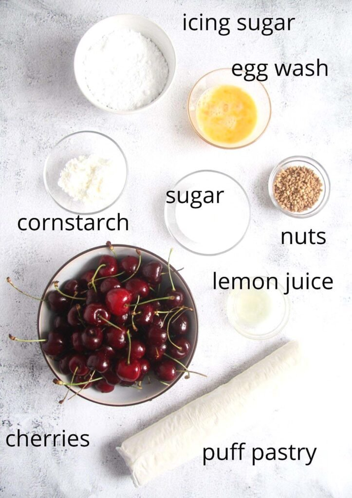 bowls with icing sugar, sugar, cornstarch, egg wash, nuts, lemon juice, cherries, puff pastry on the table.