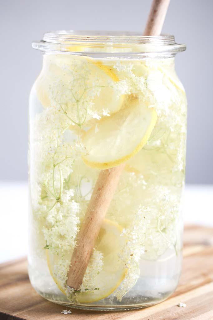 large jar with elderflowers, lemons and water, a wooden spoon inside it.