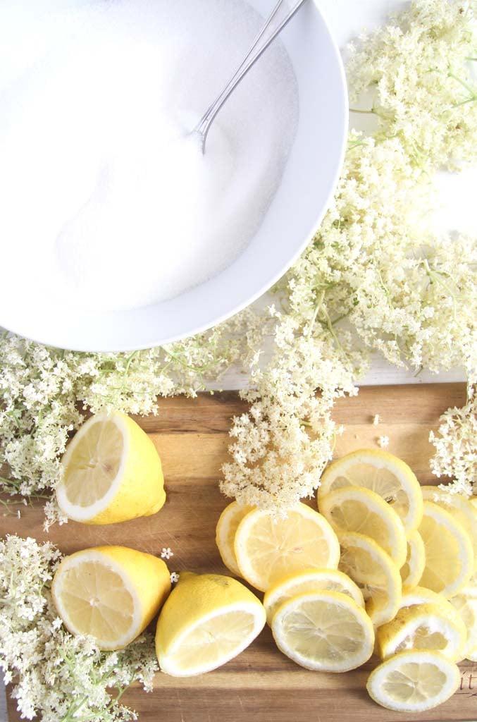 elderflowers, sliced lemons and a bowl of sugar on a wooden board.
