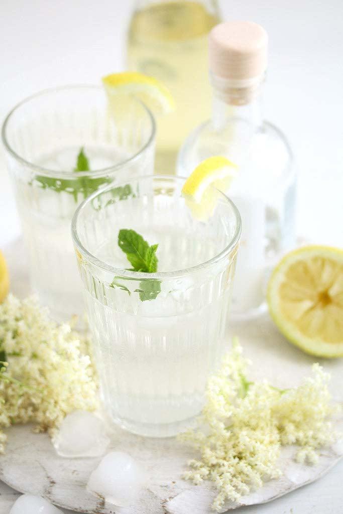 elderflower gin cocktail in two glasses, elderflowers and lemon around it.