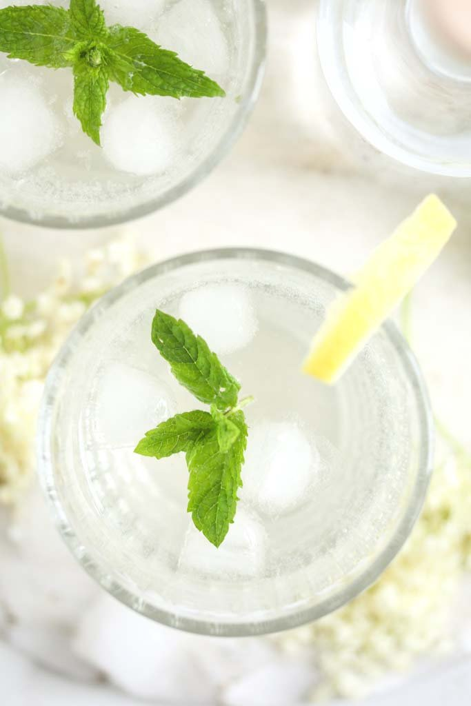 overhead view of a glass with longdrink garnished with mint and lemon wedges.