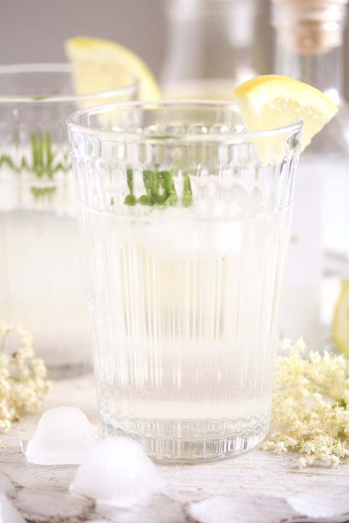 serving gin with elderflower syrup in a long glass.