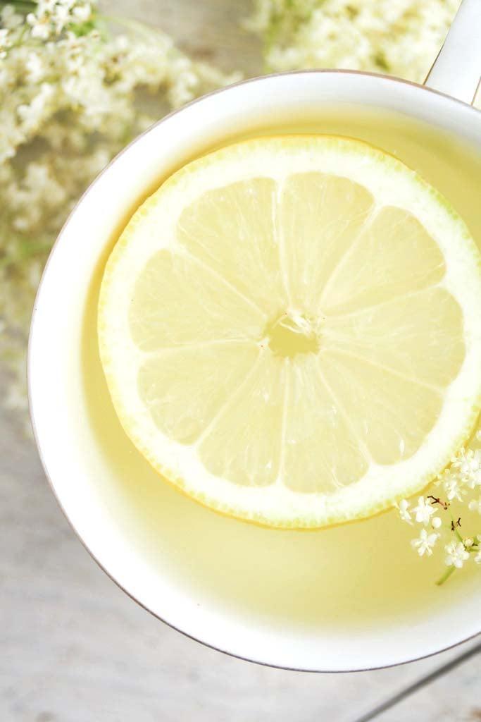 tea with elderflowers in a vintage cup with lemon slice.