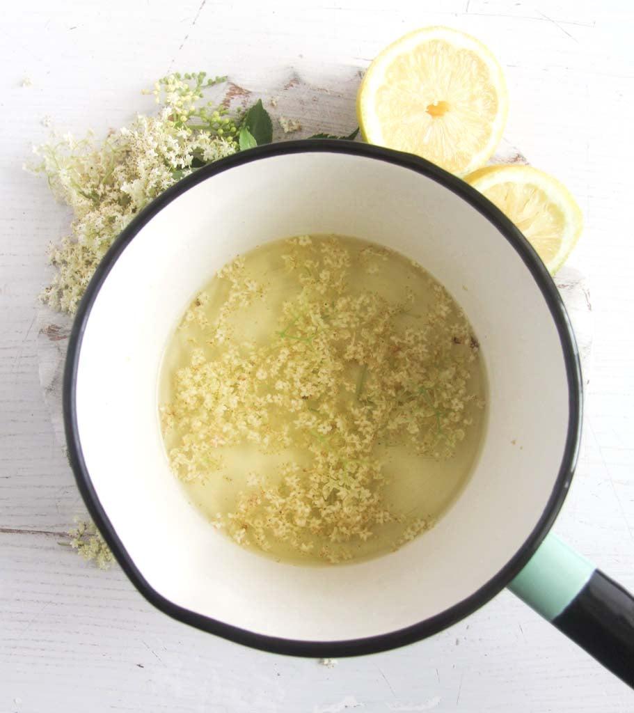 brewing herbal tea in a small saucepan, lemons and elderflowers beside it.
