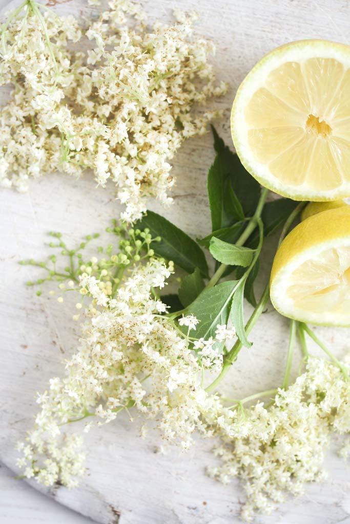 bunch of elderflowers and halved lemon on a table.