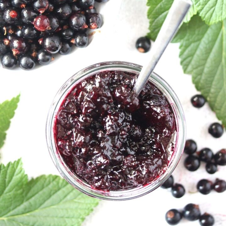 black currant jam and berries in a bowl with leaves around.