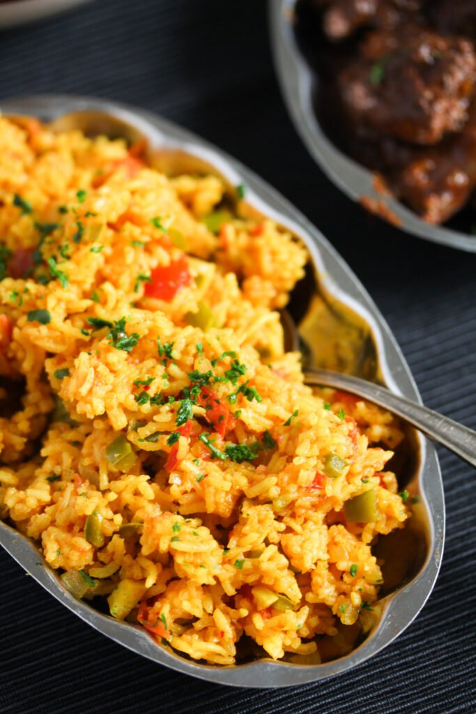 silver platter full of orange-colored rice with a spoon in it.