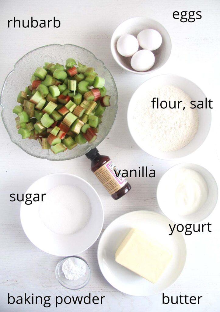bowls of chopped rhubarb, three eggs, vanilla, sugar, flour, yogurt, butter, baking powder on a table.