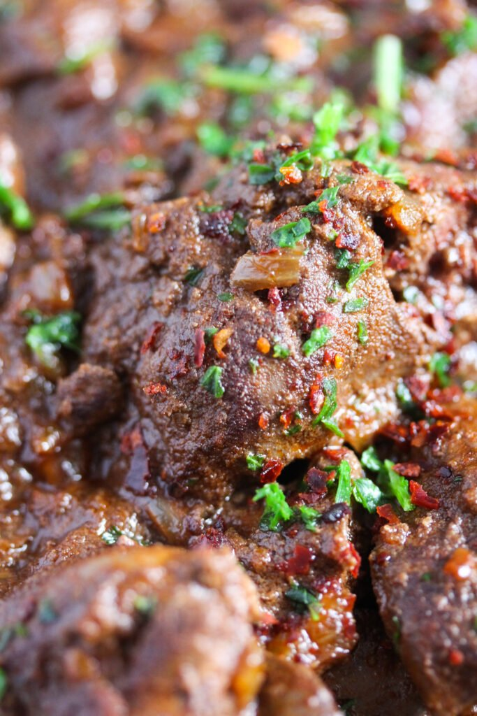 close up spicy livers sprinkled with chili and parsley.