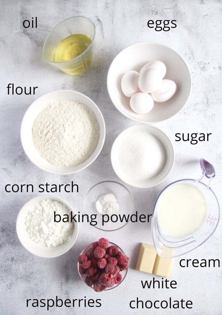 all the ingredients for making raspberry loaf cake arranged on a table.