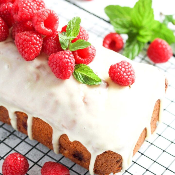 white chocolate and raspberry loaf cake on a wire rack close up.